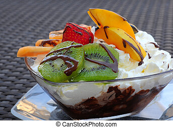 Delicious coupe with chocolate ice, fruit and whipped cream, shallow dof