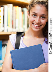 Portrait of a happy female student holding a book
