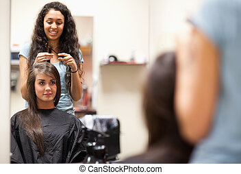 Woman combing the hair of a customer standing up