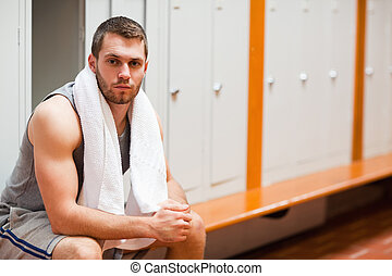 Handsome sports student sitting on a bench