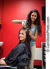 Portrait of a happy hairdresser cutting hair while looking...