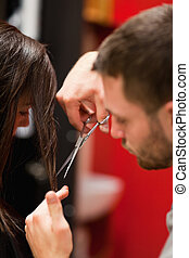 Portrait of a male hairdresser cutting hair with scissors