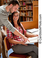 Portrait of smiling students working in a library