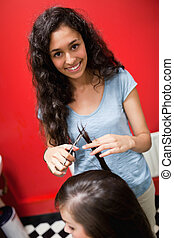 Portrait of a smiling female hairdresser cutting hair