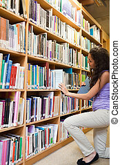 Portrait of a female student choosing a book in a library