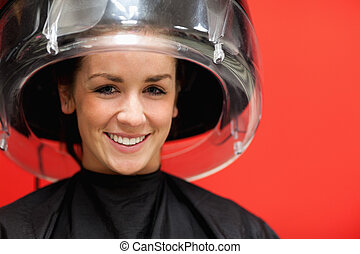 Student under a hairdressing machine while smiling at the...