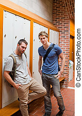 Portrait of handsome students standing up in a corridor