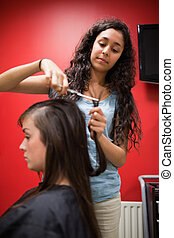 Portrait of a student hairdresser cutting hair with scissors