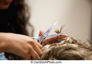 Close up of feminine hands cutting hair with scissors