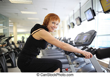 Woman exercising on bike - Happy mature woman exercising on...