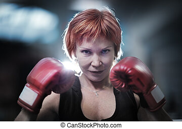 Woman boxing - Portrait of mature woman in boxing gloves...