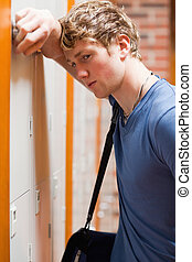 Portrait of a lonely student leaning on a locker in a...