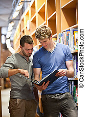 Portrait of male students looking at a book in a library
