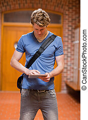 Portrait of a handsome student using a tablet computer in a...