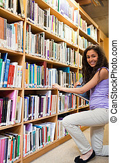 Portrait of a smiling female student choosing a book in a...