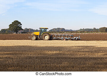plowing autumn stubble 2 - a yellow tractor plowing and...