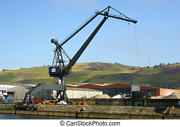 Big cargo crane at harbor with lovely colored vineyard in...