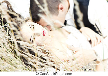 Kissing couple in grass shallow depth-of-field - Beautiful...