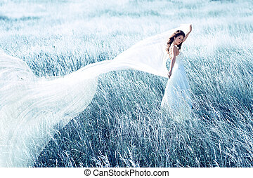 bride in blue field with waving fabric - beautiful bride in...