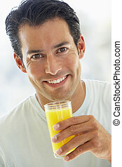 Mid Adult Man Smiling At The Camera And Drinking Orange Juice