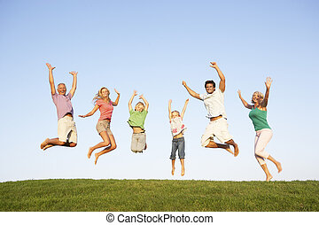 Young couple with grandparents and children jump in a field