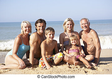 Three generation family pose on beach