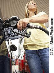Female Motorist Filling Car With Diesel At Petrol Station