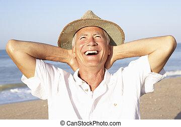 Senior man sitting on beach relaxing