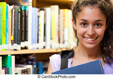 Happy female student holding a book in a library