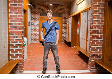 Student posing while standing up in a corridor