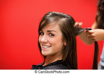 Young woman having her hair straightened while looking at...
