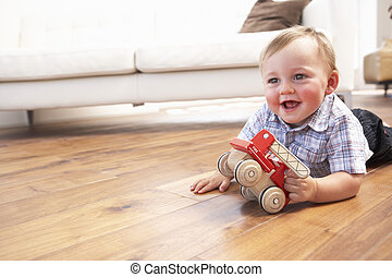 Young Boy Playing With Wooden Toy Car At Home
