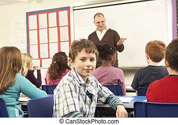 Schoolchildren Studying In Classroom With Teacher