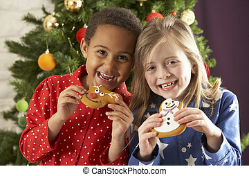 Two Young Children Eating Christmas Treats In Front Of...