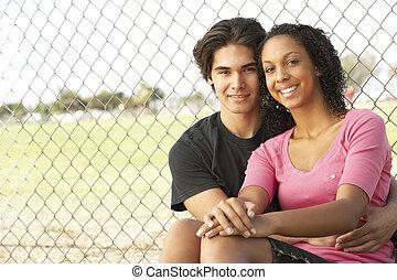 Teenage Boys Sitting In Playground