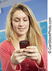 Female Teenage Student Using Mobile Phone By Lockers In...