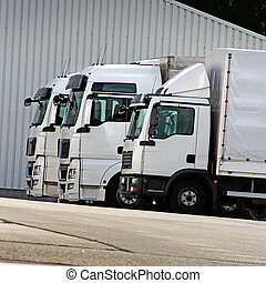 trucks - three white trucks are waiting in a row