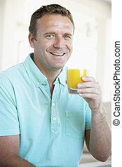 Mid Adult Man Drinking Orange Juice
