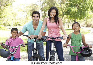 Young Family Riding Bikes In Park