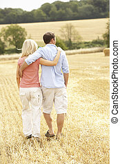 Couple Walking Together Through Summer Harvested Field