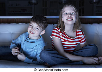 Children Watching TV Together Sitting On Sofa