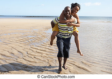 Young Man Giving Woman Piggyback Along Shoreline Of Beach