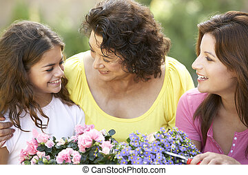 Senior Woman With Adult Daughter And Granddaughter Gardening...