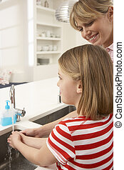 Mother And Daughter Washing Hands At Kitchen Sink