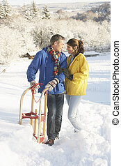 Young Couple Standing In Snowy Landscape Holding Sledge