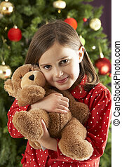 Young Girl Cuddling Teddy Bear In Front Of Christmas Tree