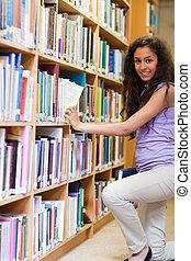 Portrait of a cute female student choosing a book in a...