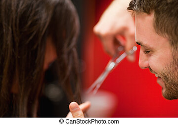 Hairdresser cutting hair with scissors