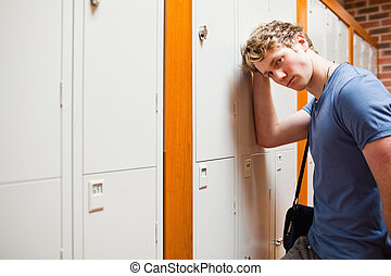 Lonely student leaning on a locker in a corridor