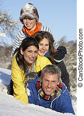 Young Family Having Fun In Snowy Landscape